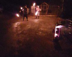 dva muži ve tmě s ohnivými koulemi